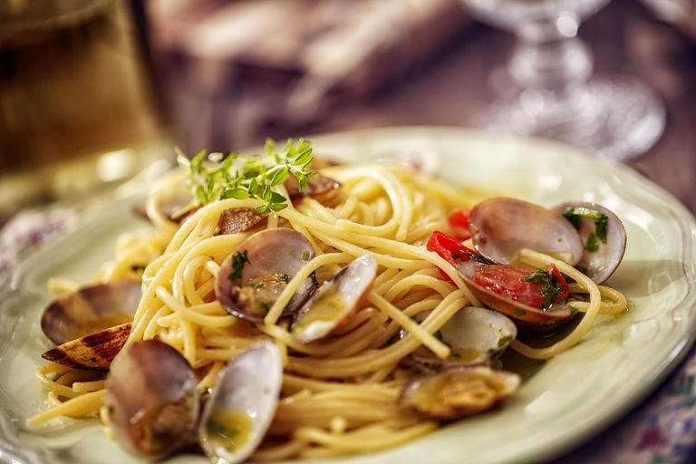 pasta and clams on a plate at a table