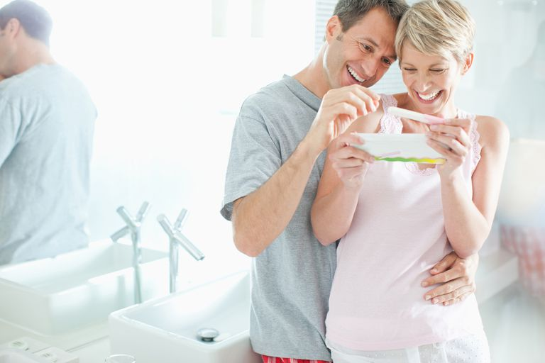 Excited couple looking at pregnancy test