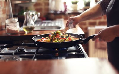 woman cooking vegetables in a pan