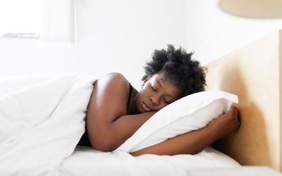 Woman sleeping in her bed at home - stock photo