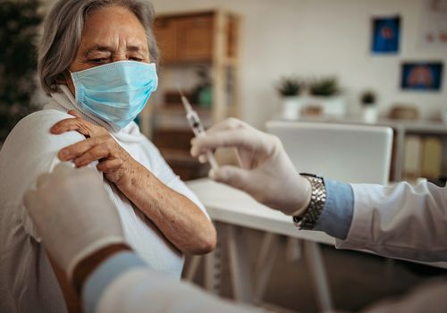Older adult woman getting a vaccine.