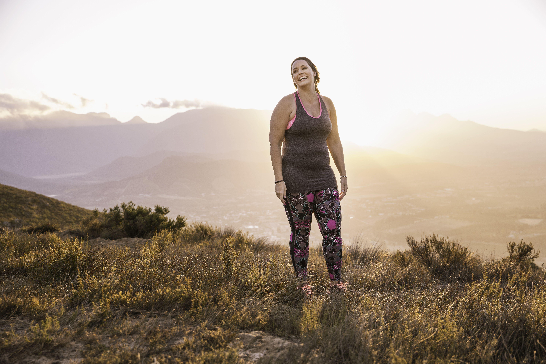 Plus size woman wearing sports clothing on mountain at sunrise