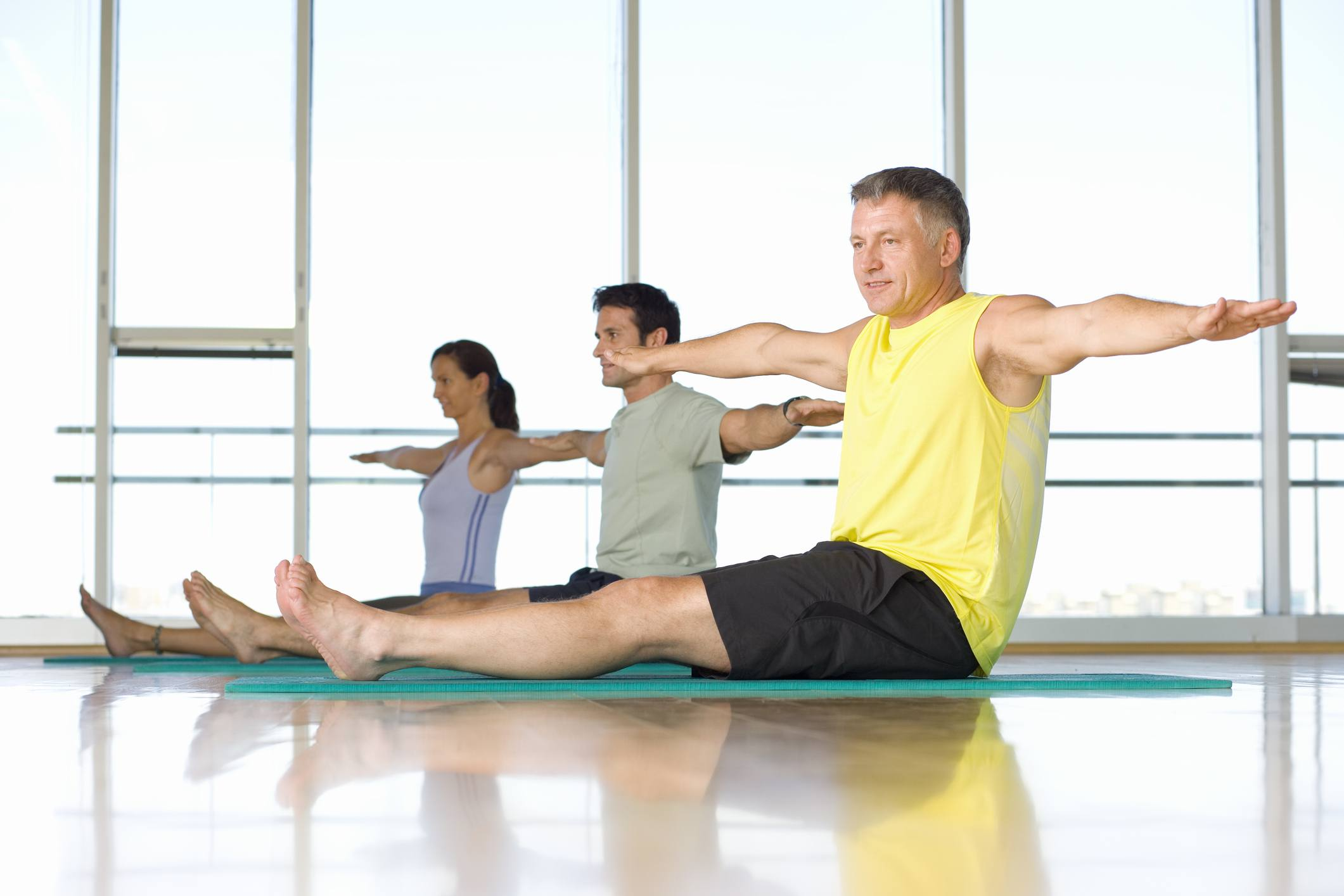 Exercise class in starting position of the pilates saw