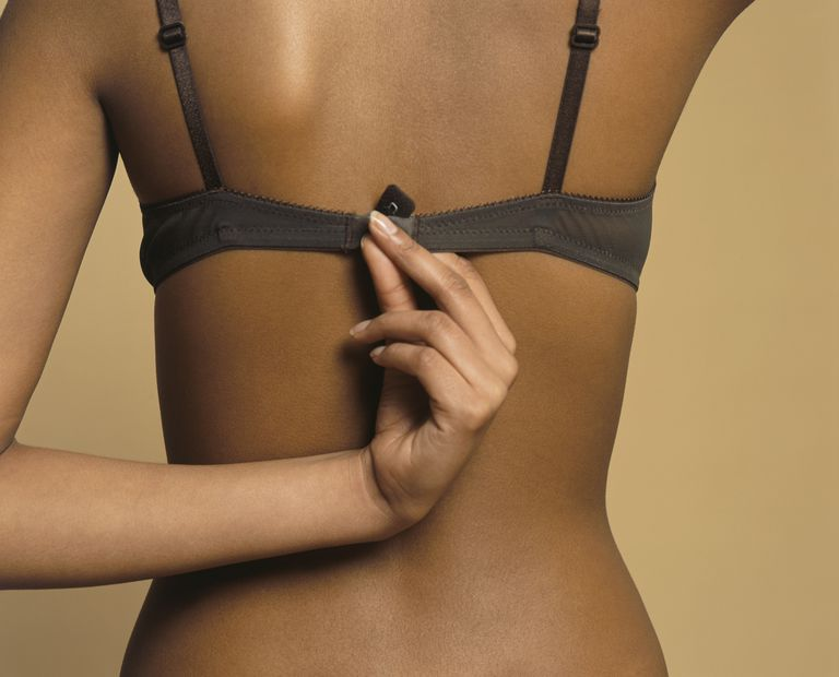woman holding bra fastener wondering if bras cause breast cancer