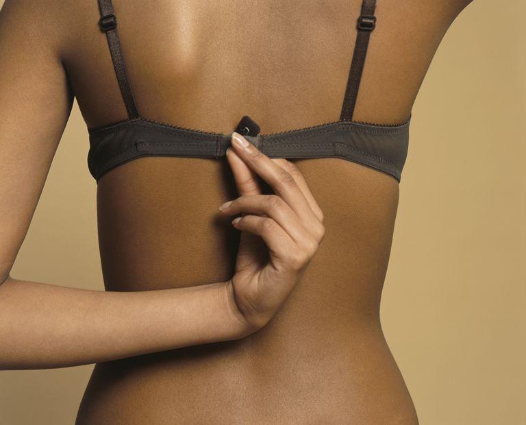5d6fb229fddc8 woman holding bra fastener wondering if bras cause breast cancer