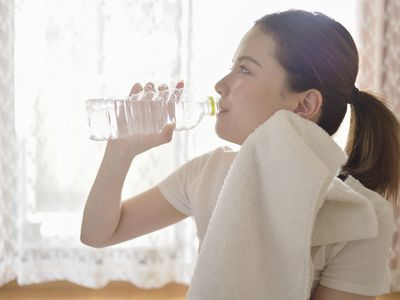 a woman drinking water in the room