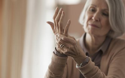 An elderly woman suffering from joint pain.