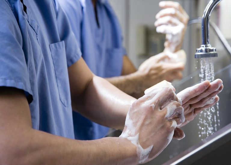 Surgeons washing hands before surgery, close-up, mid section