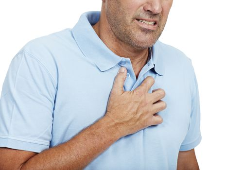 man with heartburn holding his chest in pain