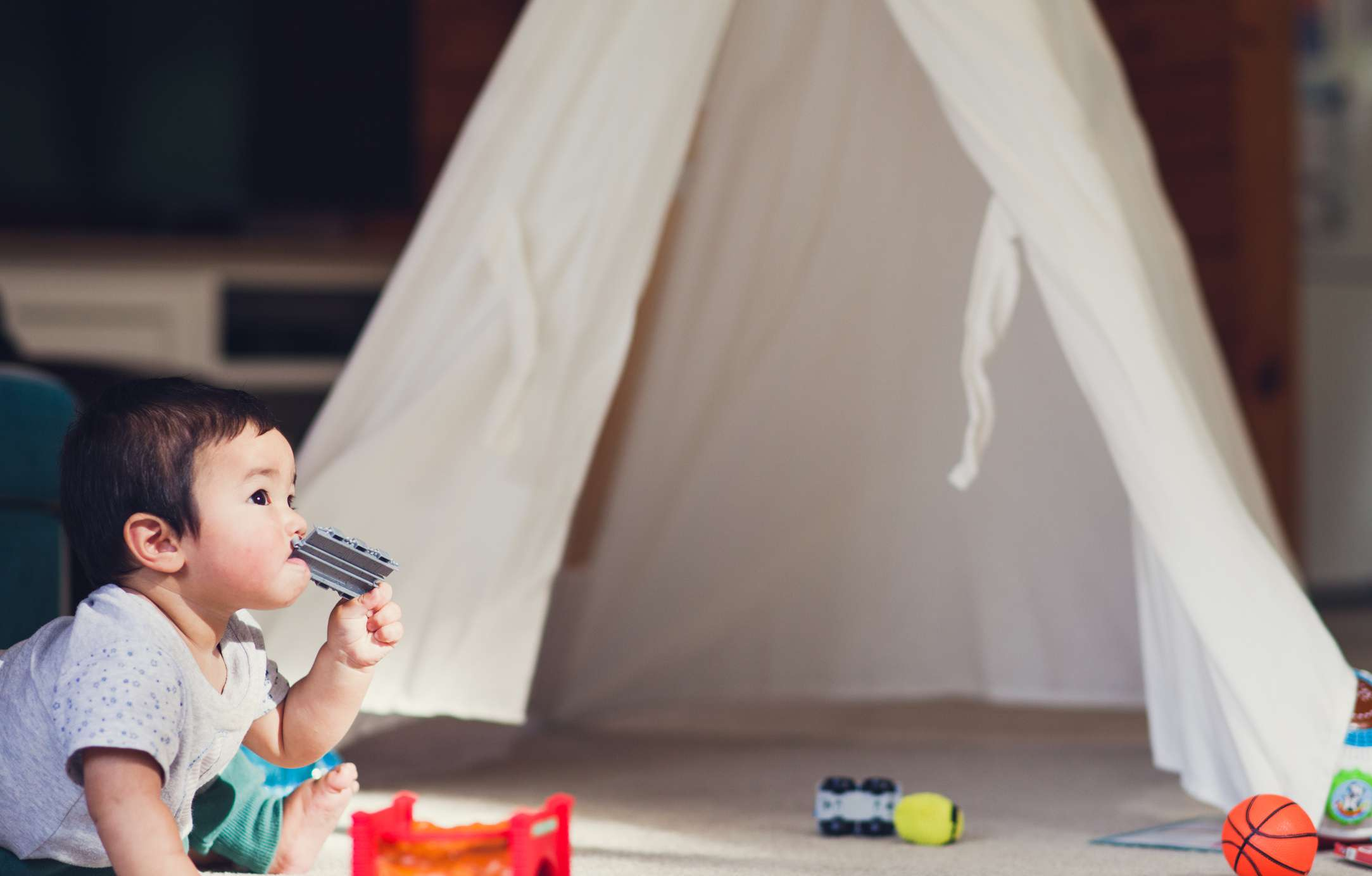 A baby sitting on the floor chewing on a toy