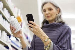 senior woman looking at medication bottle with phone in hand