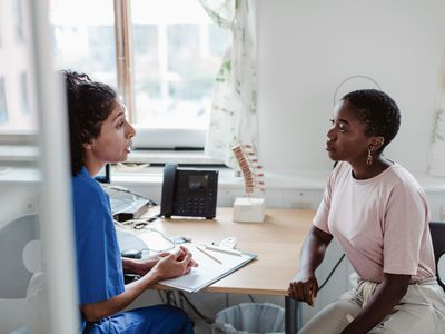 Female healthcare worker explaining medical records to young patient in office
