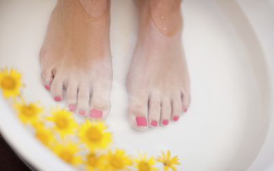 Woman soaking toes in bath with flowers