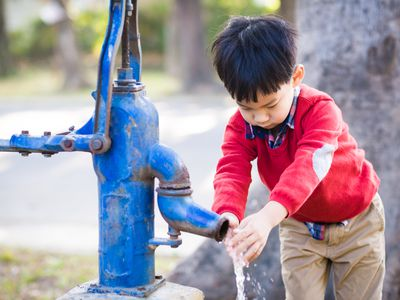 Asian boy learning to wash his hands
