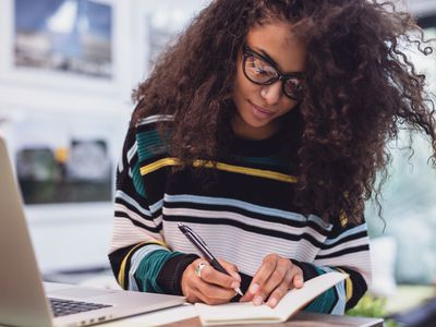Woman at a computer taking notes