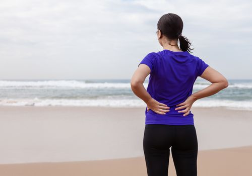 Woman holding her lower back on the beach