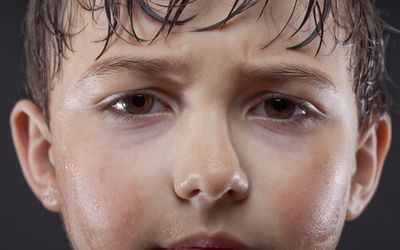 a young boy with sweat-drenched hair