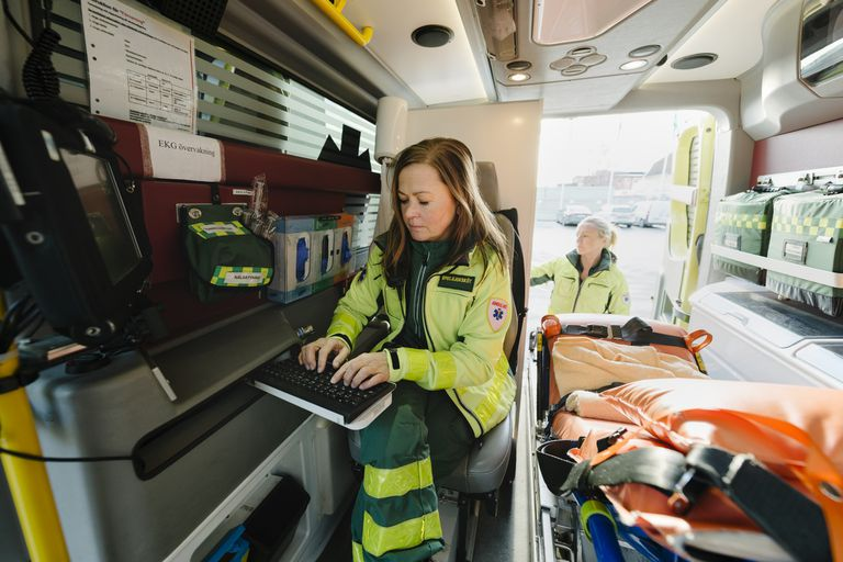 Female paramedic using computer in ambulance while colleague standing in background