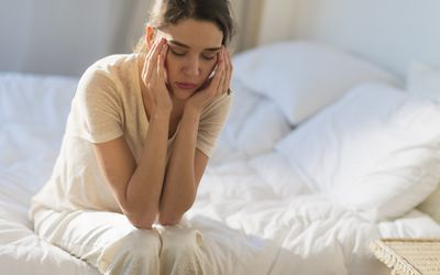 a young woman with a headache sitting on her bed