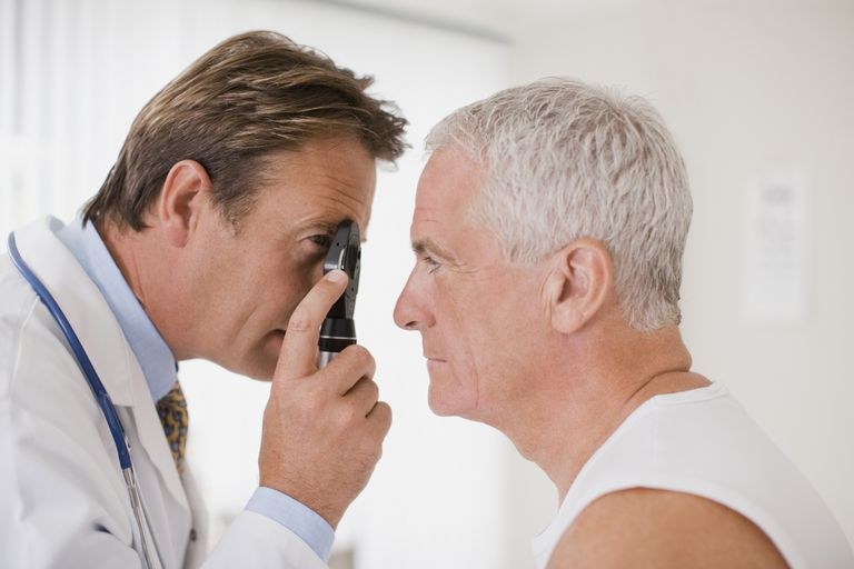 doctor looking at senior man's eye