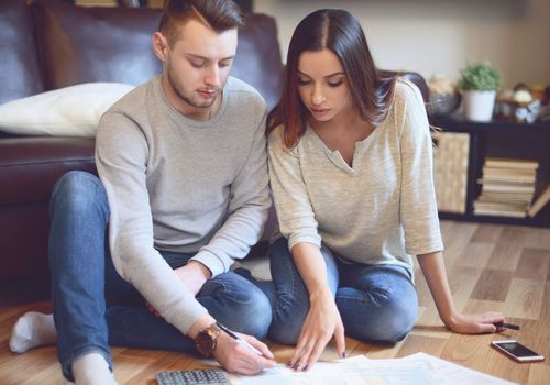 Man and woman sitting on the floor filling planning health expenses.