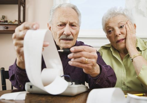 older couple looking worried looking at calculations