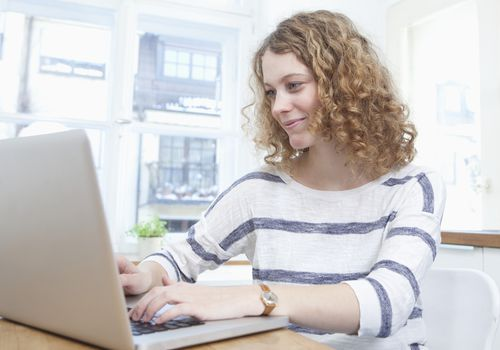 Young woman using laptop in kitchen, smiling