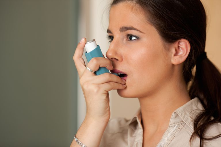 Woman using rescue inhaler