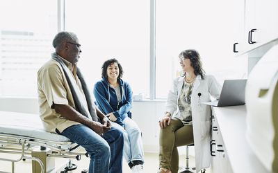 Smiling female doctor consulting with senior male patient and adult daughter in exam room