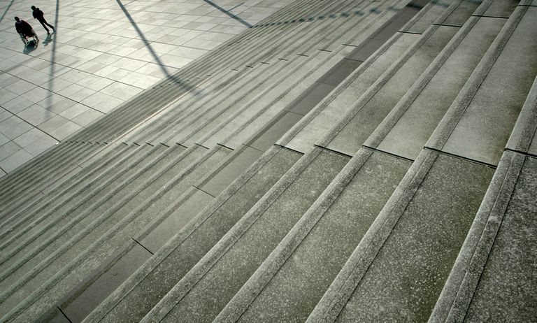 Concrete stairs and two people in the distance, one in a wheelchair