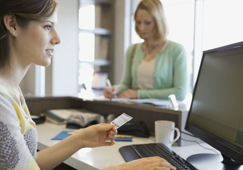A receptionist examines a patient's insurance information.