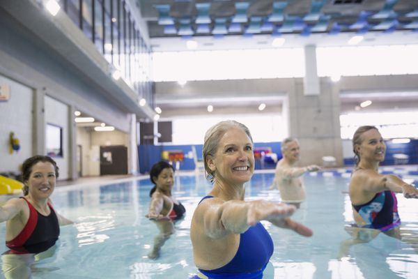 Smiling women participating in a water aerobics class