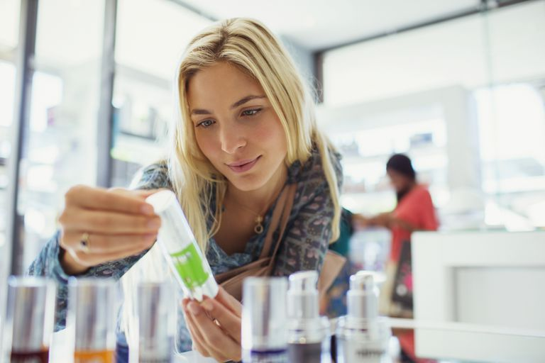 Woman looking at a product in a skin care store
