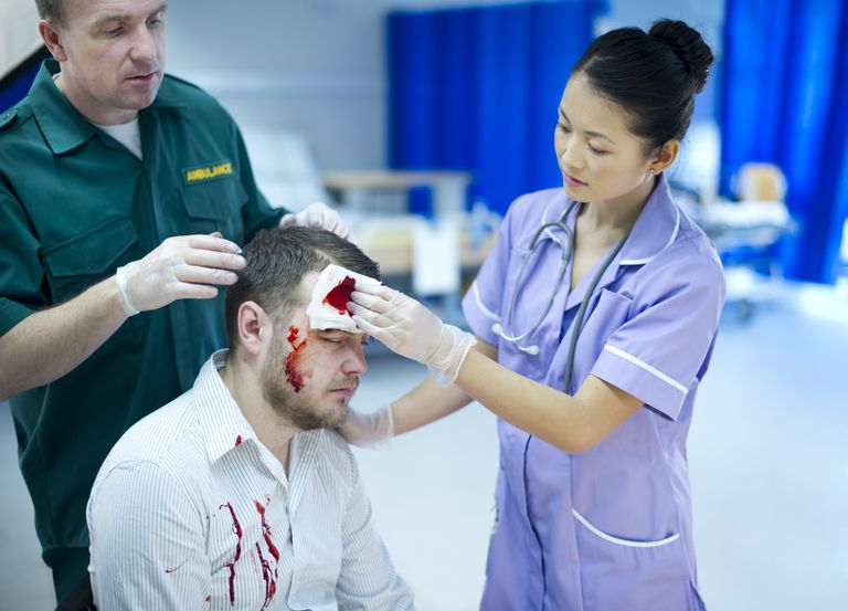 Nurse holding pressure to a head wound