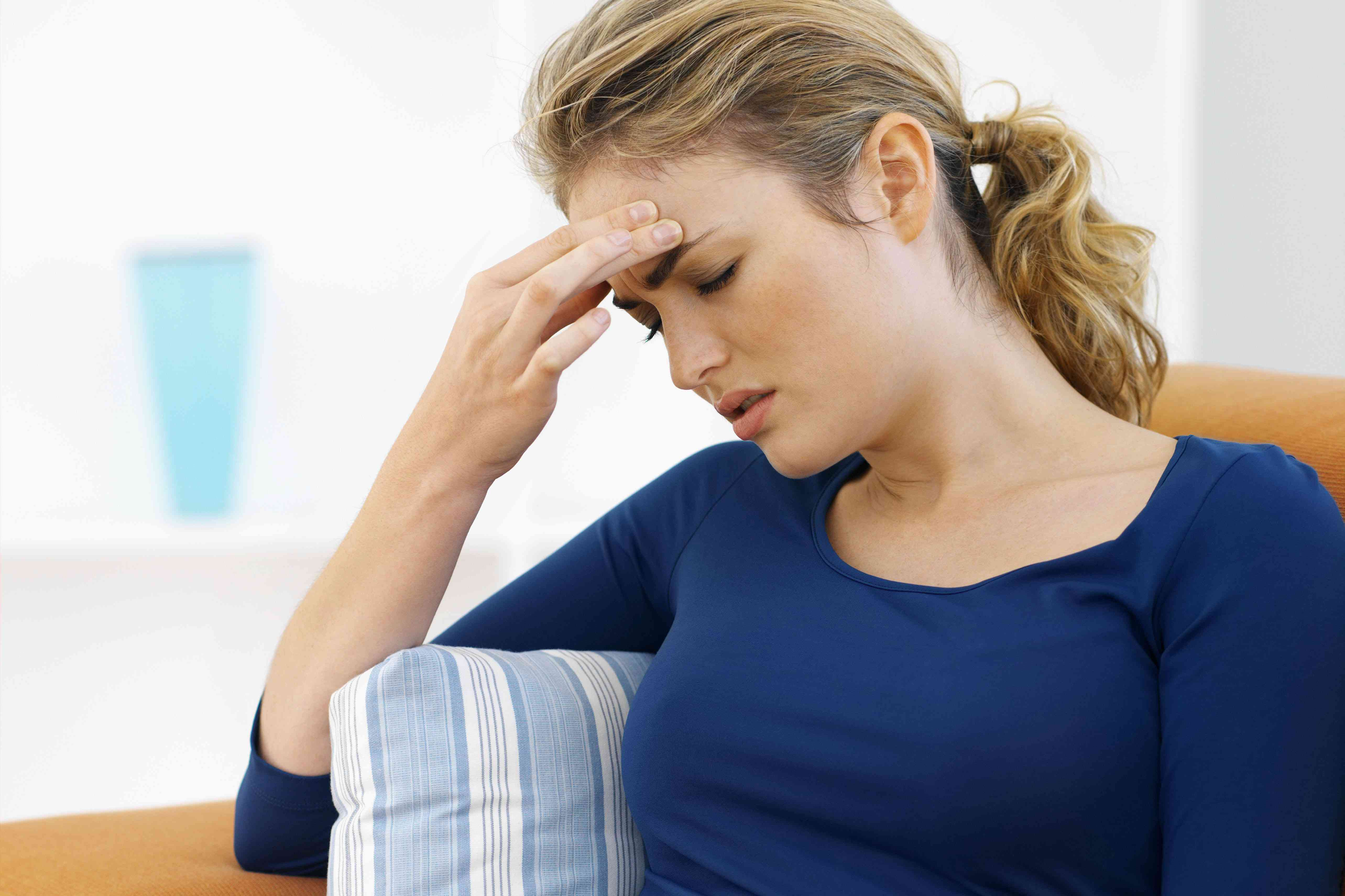 Side view of young woman sitting on sofa with hand touching head