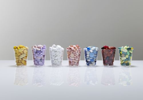 Several cups filled with pills organized by color