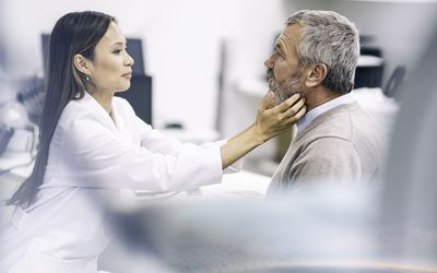 Female doctor examining an older patient's throat