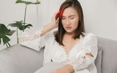 A woman sitting on a couch clutches one side of her head in pain.