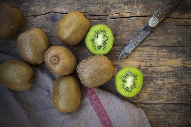Kiwis (Actinidia deliciosa) and pocketknife on wooden table