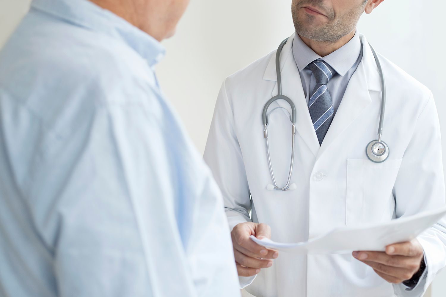 settings Male doctor holding medical notes