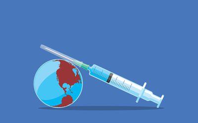 Vaccine shot resting on a globe.