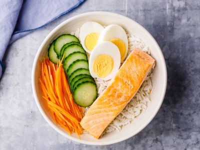 Bowl of white rice with salmon, eggs, cucumber, and carrots