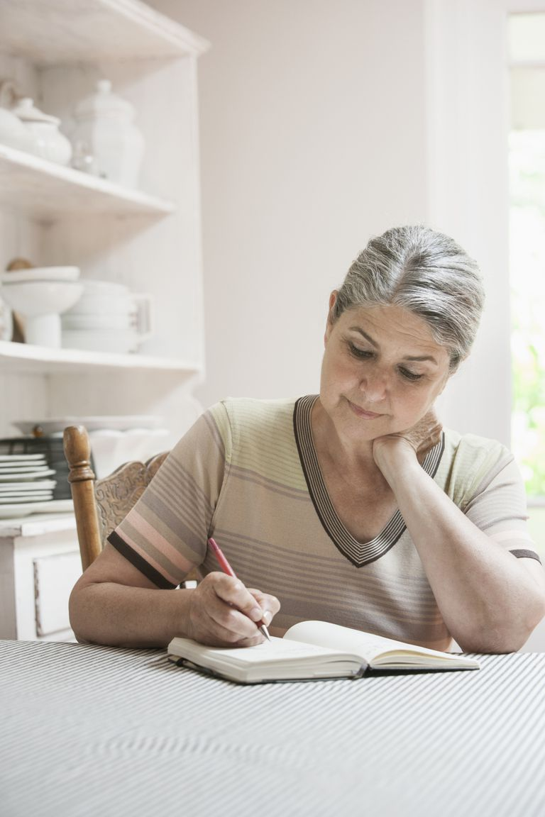 woman writing in journal at kitchen table