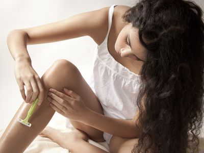 Young woman shaving legs