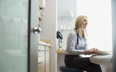 Female doctor with medical record sitting examination room