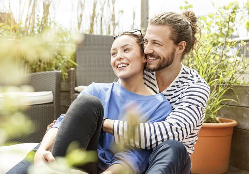 Young couple relaxing on their balcony, embracing