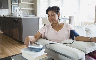 Woman checking blood pressure in living room.