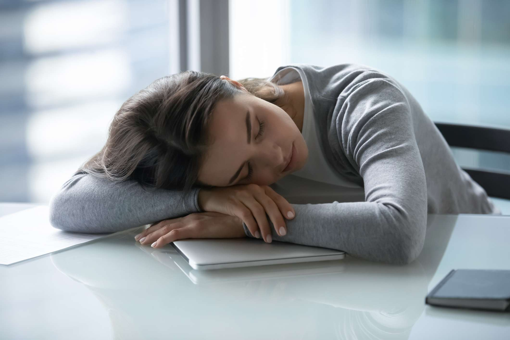 Young businesswoman falling asleep at work desk