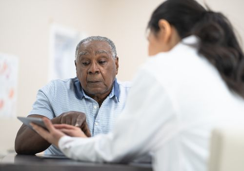 Doctor showing information to a senior man about survival rates