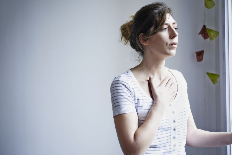 Woman with breathing difficulties puts hand on chest
